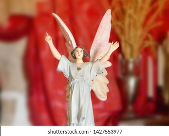a female Art Nouveau angel in a chapel, with arms and hands raised high, large upturned wings, small porcelain figurine. The background in dark red, very soft with bokeh from a red velvet curtain.