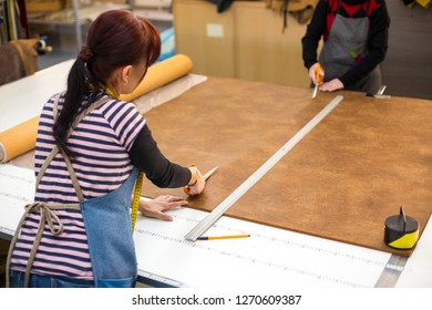 Female artisan cutting brown leather with scissors