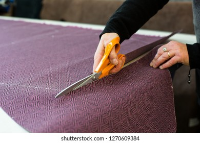 Female artisan cutting violet fabric with scissors - close up