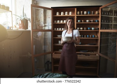 Female artisan laughing and holding a stack of ceramic plates while standing in front of display shelves in her pottery shop