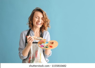 Female artist with brush and paint palette on color background