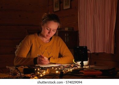 female artist drawing artwork at home at night, cozy cottage atmosphere, matching footage also available in portfolio
