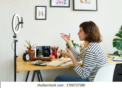 Female artist filming illustration process at home. Creative blogger working from home making master-class using ring lighting. Cozy artist's studio.