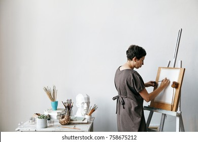 Female artist in her spacious white studio working with watercolor painting.  Natural lighting. Disclosure of creativity concept. Horizontal composition with copy space.