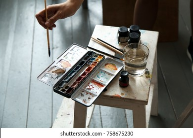 Female artist in her spacious white studio working with watercolor painting.  Natural lighting. Disclosure of creativity concept. Horizontal composition. Close up