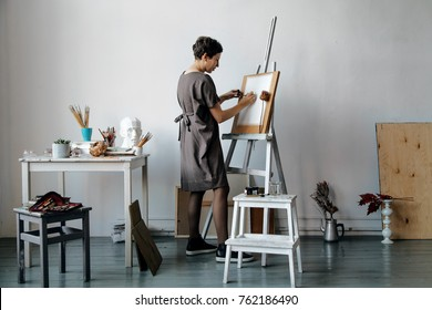 Female artist in her spacious white studio working with watercolor painting.  Natural lighting. Disclosure of creativity concept. Horizontal composition.