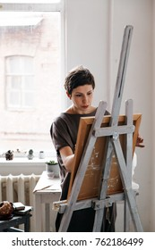 Female artist in her spacious white studio working with watercolor painting.  Natural lighting. Disclosure of creativity concept. Vertical composition.