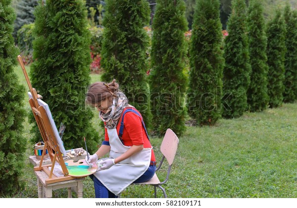 Female artist holds brush and wrote oil on canvas painting, does what likes, interests and hobbies,  preparing picture to order, advertises or art studio for drawing utensils, sits on chair at  wood