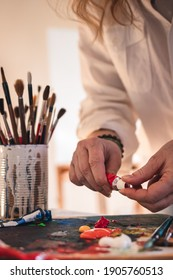 Female artist mixing acrylic colors on palette for painting. Woman working in art studio. Palette and paintbrush on table