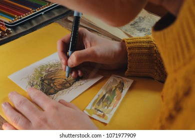 female artist painter paiting a watercolor picture of a bear