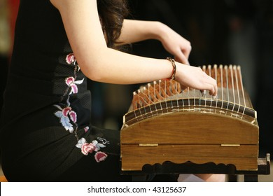A female artist playing the Guzheng, a traditional chinese musical instrument at a Chinese New Year celebration.