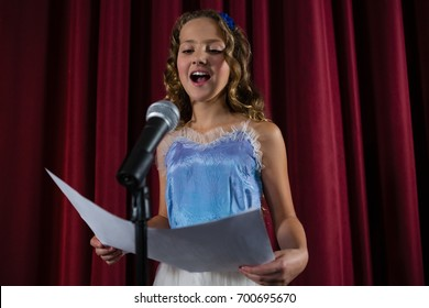 Female artist singing song on stage in theatre