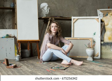 Female artist sitting and smiling in the studio next to empty canvases. Portrait of a woman at work