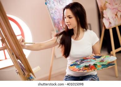 Female Artist Working On Painting In Studio