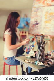 Female Artist Working On Painting In Studio. Background image, selective focus on foreground
