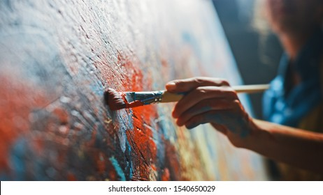 Female Artist Works on Abstract Oil Painting, Moving Paint Brush Energetically She Creates Modern Masterpiece. Dark Creative Studio where Large Canvas Stands on Easel Illuminated. Low Angle Close-up