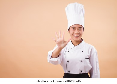 female asian chef pointing up five fingers gesture