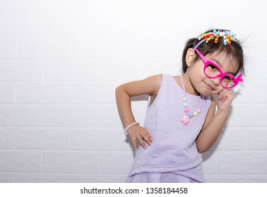 Female asian child girl posing wacky thinking pose while wearing some accessories like crown, necklace and wearing purple dress while having fun