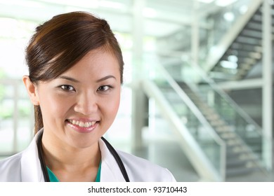Female Asian doctor wearing a white coat and stethoscope.