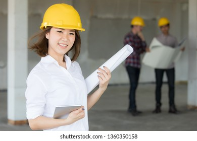 Female Asian enginee holding blueprint plan and tablet computer in hands standing and smiling with selt confident while two male team talking in blur background in construction site.