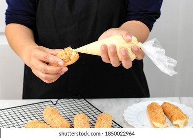Female Asian Hand Filling Frech Pastry Craquelin Eclair Profiterolle with Cream using Pastry Bag. Home Baking Preparation Baking Choux Pastry/Cream Puff.