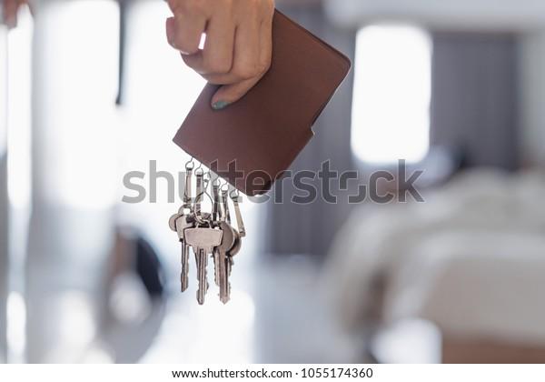 寝室に茶色の革のキーホルダーを持つアジアの女性の手