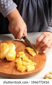 Female Asian Hand Slicing Diced Yellow Ripe Jackfruit. COncept preparation Making Thai or Indonesian Sweet Dessert, Es Campur, Es Buah, or Es Oyen
