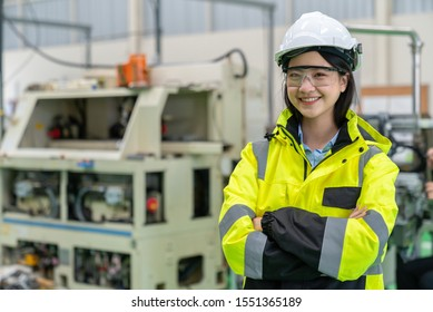 Female asian Industrial Engineer wearing Hard Hat, Safety Jacket , Glasses safety and Smiling Looking at camera in Industry Factory.