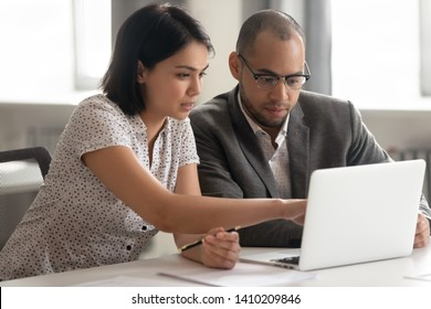 Female asian mentor teaching african male trainee intern looking at laptop, manager consulting client pointing at computer, teacher supervisor explaining online work to coworker sit at office desk