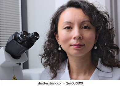 Female asian scientist with microscope behind her