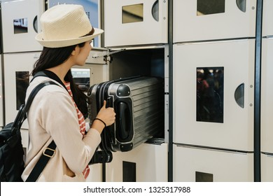 female asian visitor in casual wear and straw hat putting the luggage in the locker. half-body upper view young girl travel backpacker using lock box in airport release heavy suitcase indoor tourism