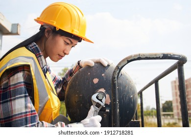 A female Asian worker wearing a yellow vest and helmet is servicing an industrial air tank in the sunny outdoors.