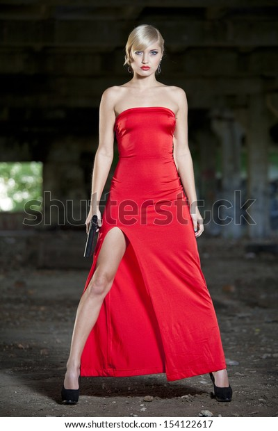 Female assassin in vintage look with gun in old fabric ruins
