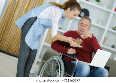 female assistant giving a cup of coffee to disabled male