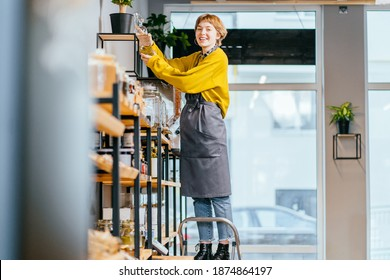 Female assistant in grey apron working in sustainable small local business. Female seller of zero waste shop. Woman standing on a stepladder, watering flowers in a pot in plastic free grocery store.
