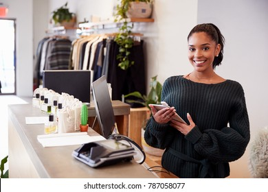 Female assistant smiling from the counter in clothing store