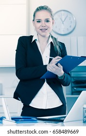 Female assistant standing in office and noting tasks