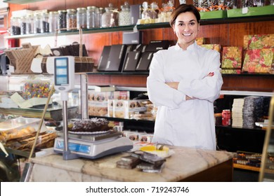 Female assistant weighing on scales festive chocolate cake in confectionery