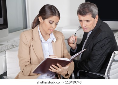 Female assistent checking appointments for manager in datebook