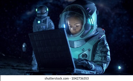 Female Astronaut Wearing Space Suit Works on a Laptop, Exploring Newly Discovered Planet, Communicating with the Earth. In the Background Her Crew Member and Living Station. Colonization Concept.