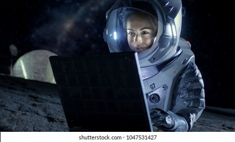 Female Astronaut Wearing Space Suit Works on a Laptop, Exploring Newly Discovered Planet, Communicating with the Earth. In the Background Space Habitat. Colonization Concept.
