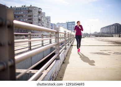 Female athelete running in city enviroment