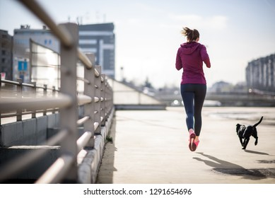 Female athelete running in city enviroment with her dog