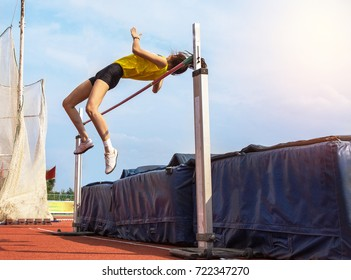 female athlete in action high jump over bar in track and field