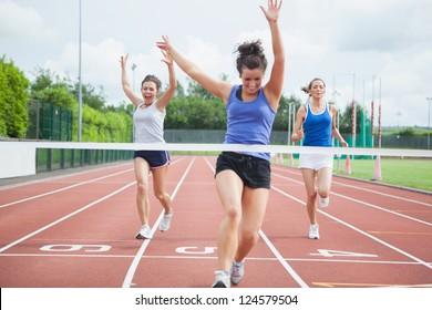 Female athlete celebrates win at finish line at track field