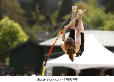 A female athlete competing in the pole vault at a track and field event.