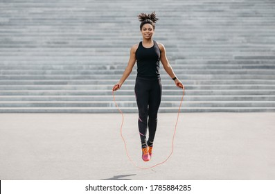 Female athlete does cardio workout. Smiling african american girl in sportswear with fitness tracker jumping rope outdoors, free space