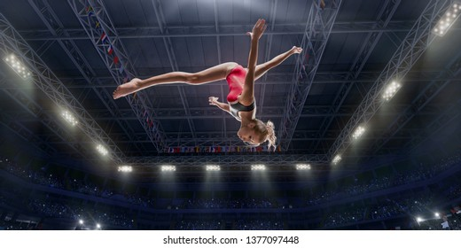 Female athlete doing a complicated exciting jump trick in a professional gym. Girl perform stunt in bright sports clothes