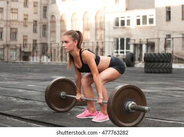 Female athlete doing crossfit deadlifts