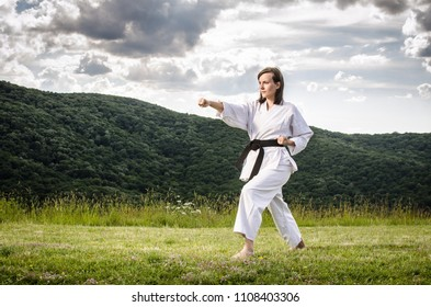 Female athlete doing karate exercise outdoors. Martial arts.